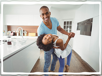 happy African American couple dancing in kitchen