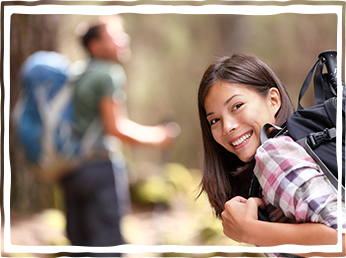 young woman wearing backpack hiking smiling